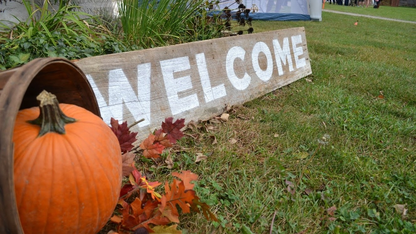 Pumpkin on glass with wooden welcome sign
