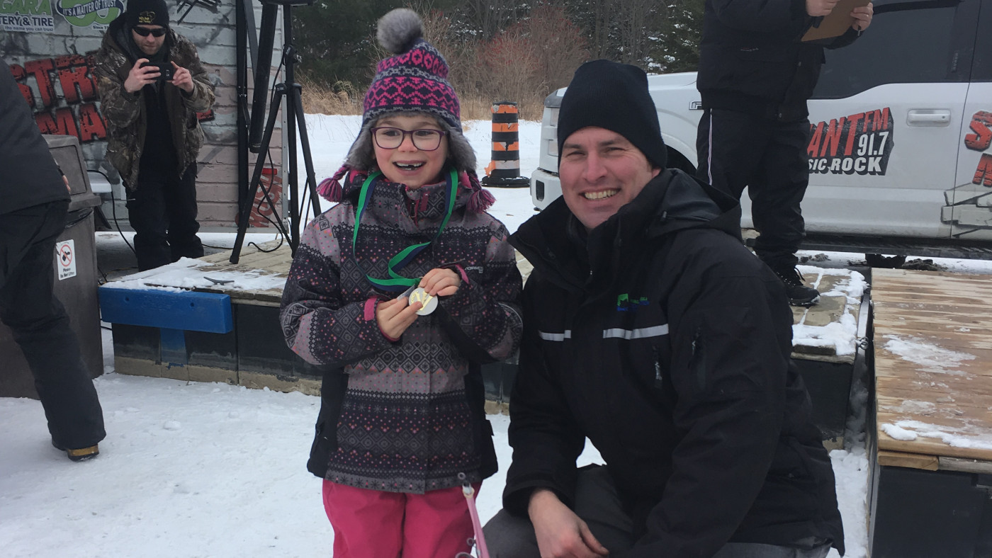 Binbrook Superintendent poses with little girl, winner of ice derby prize