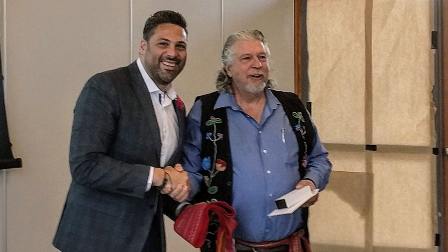 Board chair shakes hand of Metis partner