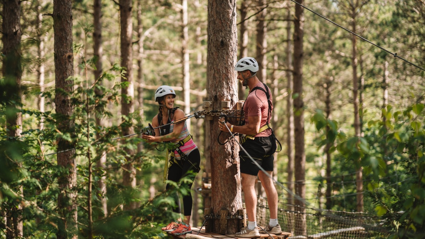Photo of two people on Treetop Trekking adventure surrounded by green trees, brown branches