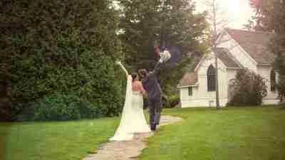 Bride and groom walk towards wedding chapel with hands in the air.