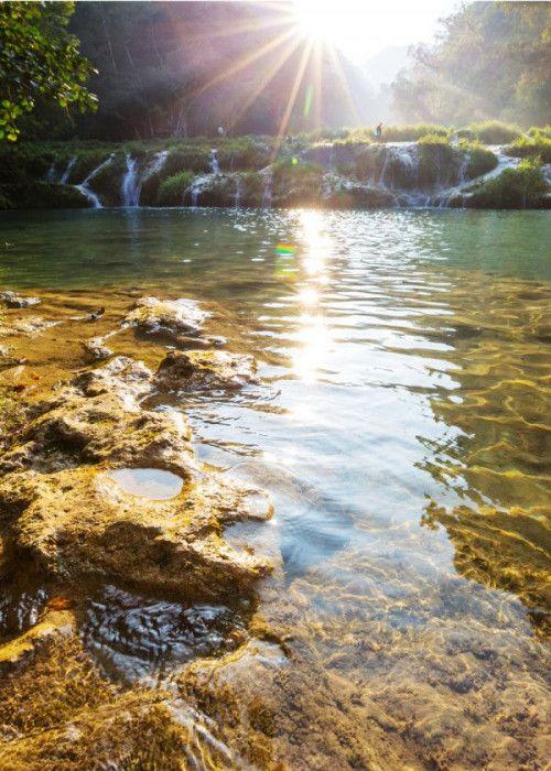 Sun beaming down on shoreline of river.