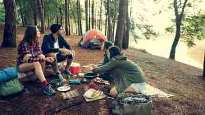 Friends outside of their tent make breakfast in the woods.