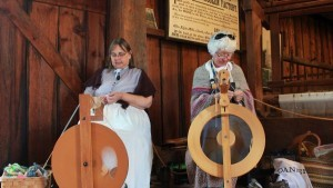 Two ladies demonstrating handweaving and spinning with equipment