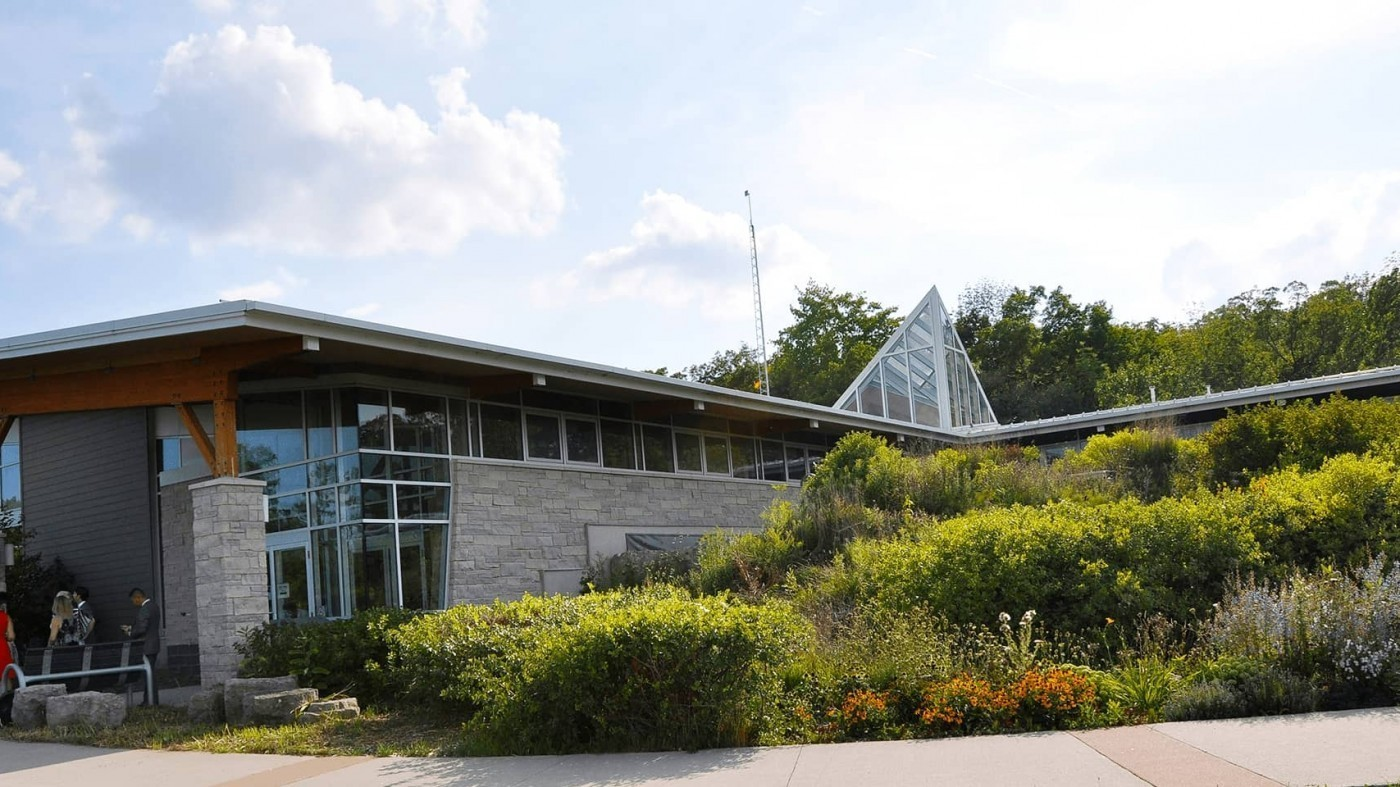 centre for conservation at balls falls surrounded by green blooms and blue cloudy skies