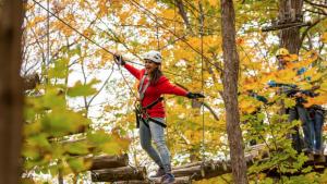 Girl in red sweater walking on wood bridge amongst the trees