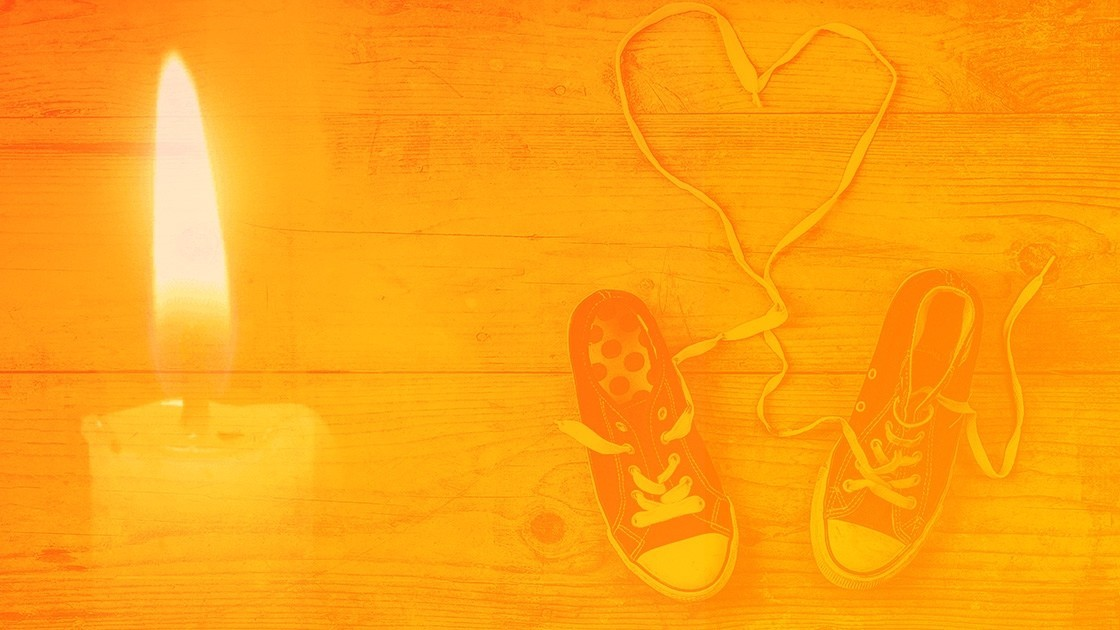 Orange Background with Lit Candle and Child Shoes