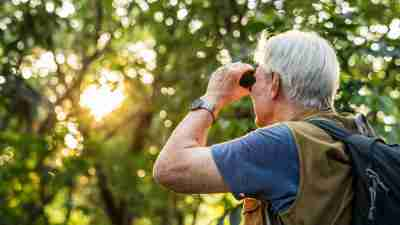 Man looks towards trees with binoculars.
