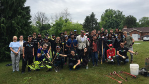 Group of individuals posing with tree planting tools