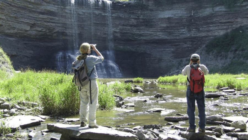 Two individuals looking up at waterfall