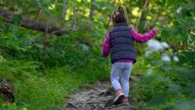 little girl walking through green forest trails