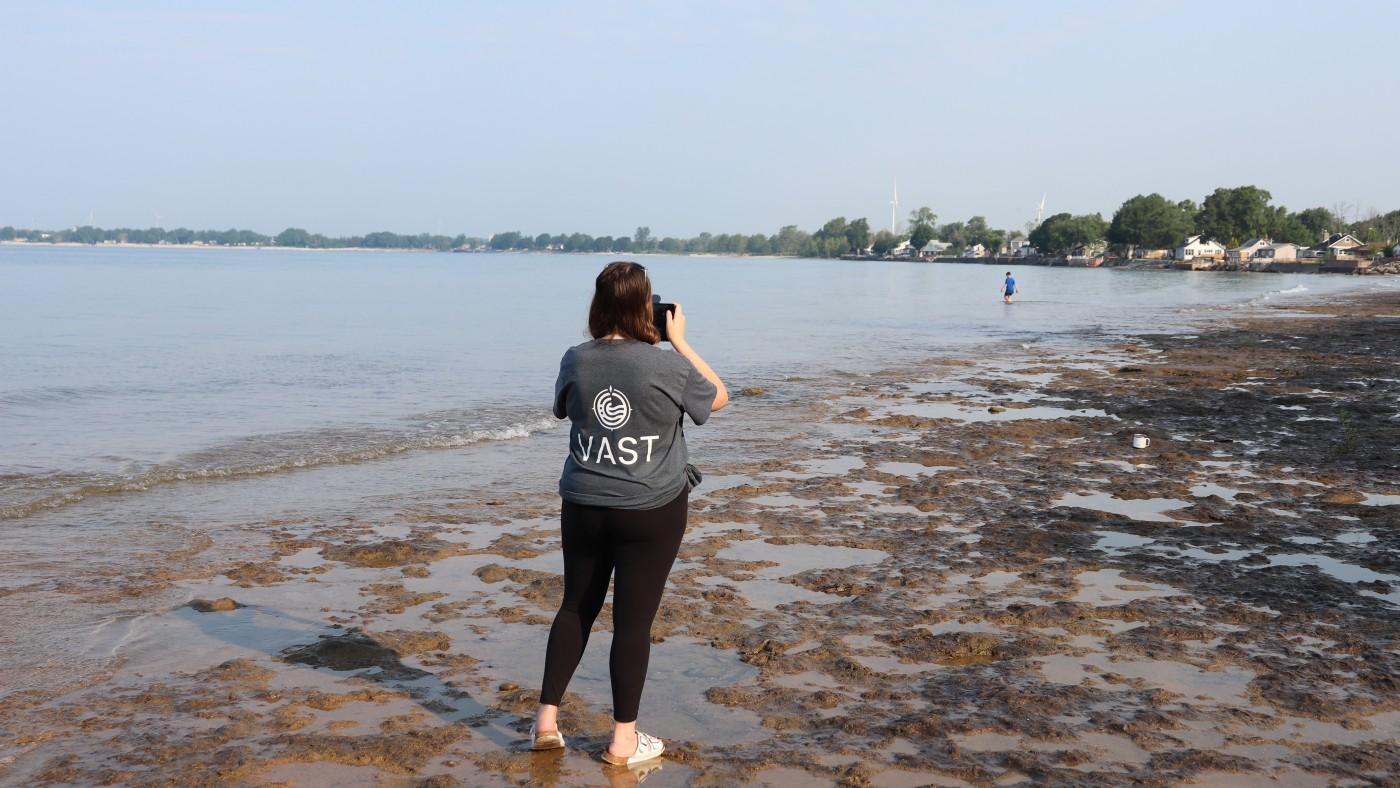 Photo of Citizen Scientist Using VAST- Wearing a grey tshirt, standing by Lake Erie beach shoreline
